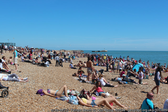 Sunbathers on Pelham Beach, Hastings under a cloudless sky.